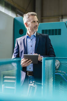 Businessman holding a tablet in a factory looking around - DIGF10128