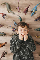 Portrait of anxious little boy lying on the floor between toy dinosaurs - JRFF04404