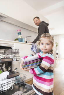 Daughter clearing the dishwasher, father in the background - SDAHF00771