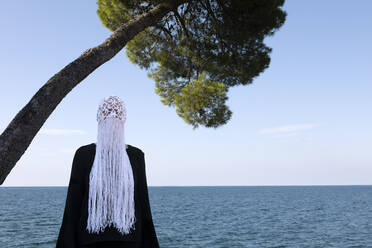 Woman wearing crocheted white headdress with fringes standing in front of the sea - PSTF00686