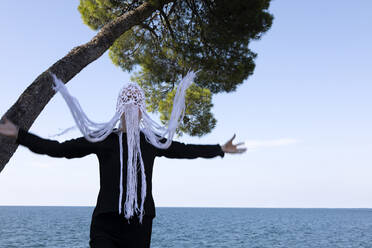 Woman wearing crocheted white headdress with fringes standing in front of the sea moving - PSTF00689
