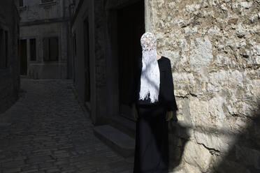 Woman dressed in black wearing crocheted white headdress with fringes, Rovinj, Croatia - PSTF00695
