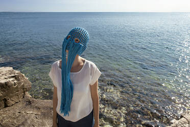 Woman wearing crocheted blue headdress with fringes standing in front of the sea looking up - PSTF00698