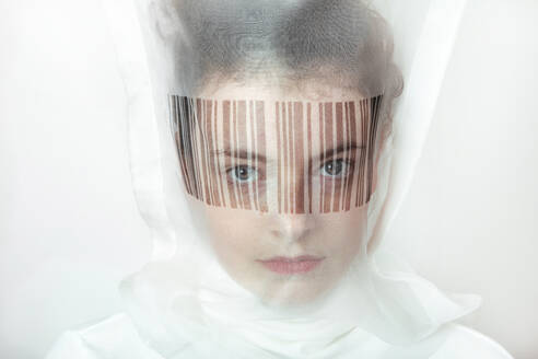 Portrait of young woman wearing  transparent mask with bar code - PSTF00716
