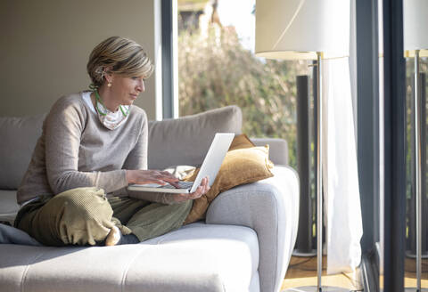 Woman using laptop while sitting on sofa in living room during working from home - BFRF02233