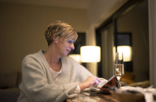 Blond woman working late while using digital tablet in illuminated living room - BFRF02242