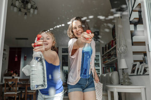 Two sisters splashing with window cleaner - OGF00300