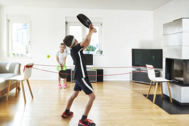 Siblings playing tennis with frying pans in living room at home during quarantine - DIKF00471