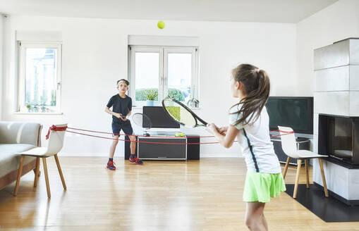 Brother and sister playing tennis at home while exercising during quarantine - DIKF00474