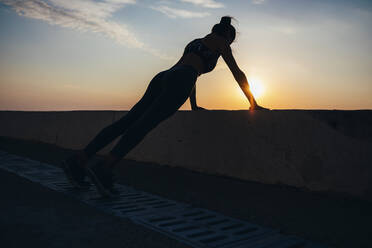 Silhouette woman doing push-ups at promenade during sunrise - OYF00136