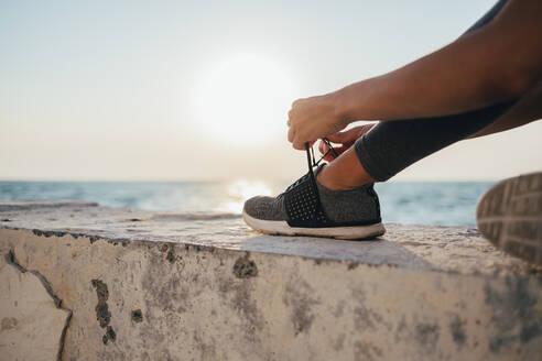 Low section of female athlete tying shoelace on promenade - OYF00142