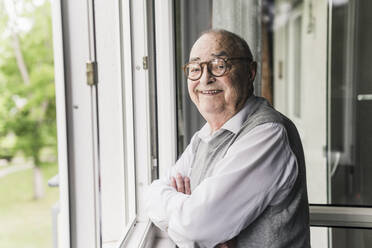 Portrait of smiling senior man standing at open window - UUF20220