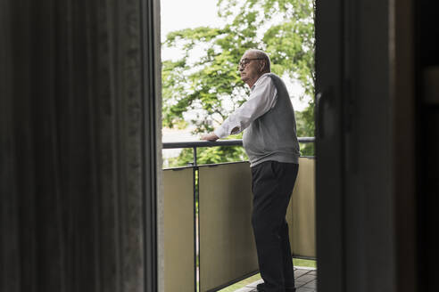 Senior man standing on balcony looking at distance - UUF20223