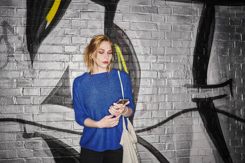 Young woman using smart phone while standing against graffiti wall at night - MMIF00260