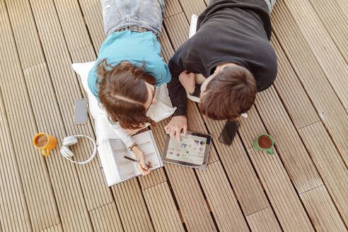 Teenage couple lying on terrace learning together with digital tablet - STDF00223