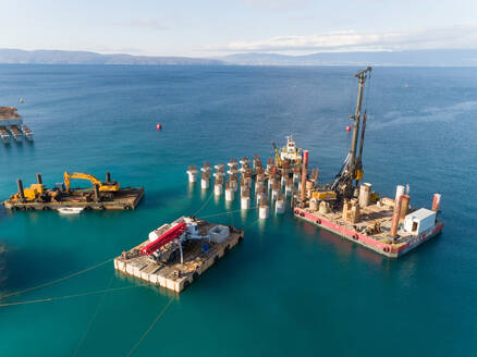 Aerial view of machinery at the construction of future LNG terminal on the shore of the bay in Omisalj, Croatia - AAEF08202
