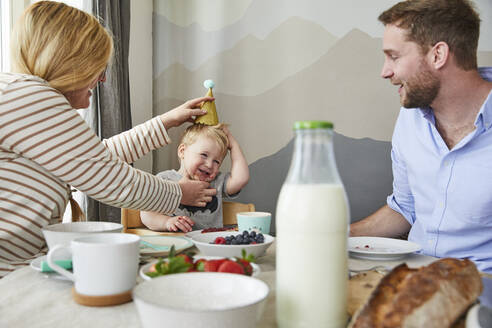 Portrait of little boy having fun with his parents at breakfast table - FSF01053