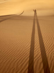 Shadow of a man and a woman on the desert sand, Walvis Bay, Namibia - VEGF02069
