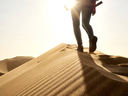 Low section of woman waking on the ridge of a dune in the desert, Walvis Bay, Namibia - VEGF02075