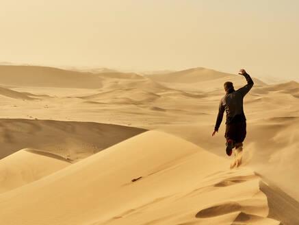 Man running on a dune in the desert, Dune 7, Walvis Bay, Namibia - VEGF02084