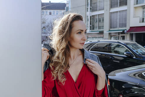 Portrait of woman in red dress in the city - OGF00310