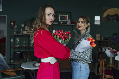 Portrait of two women with red tulips in a flower shop - OGF00334