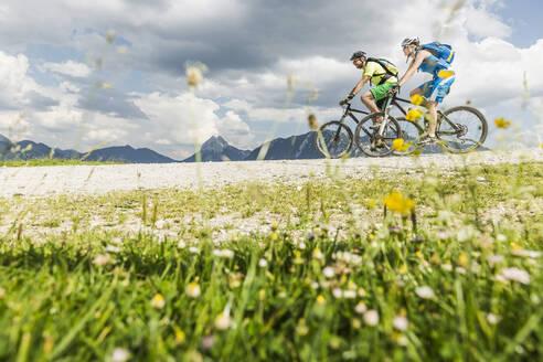 Couple mountainbiking on gravel path in the mountains, Achenkirch, Austria - SDAHF00826