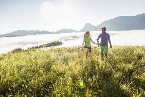 Couple hiking on a meadow in the mountains at sunrise, Achenkirch, Austria - SDAHF00889