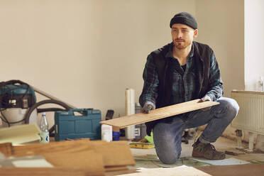 Man refurbishing shop location, laying flooring - MCF00790