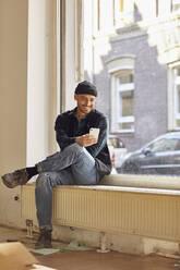 Man refurbishing shop location, sitting on windowsill, using smartphone - MCF00793