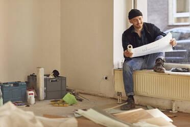 Man refurbishing shop location, sitting on windowsill, studying blueprint - MCF00799