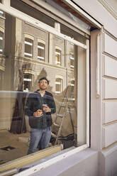 Man refurbishing shop location, drinking coffee, looking out of window - MCF00808