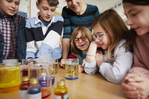 Group of children with teacher in a science chemistry lesson - PWF00065