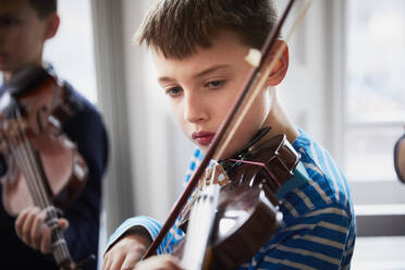 Boy playing violin during a lesson - PWF00089