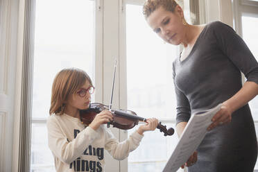 Teacher teaching boy playing violin during a lesson - PWF00095