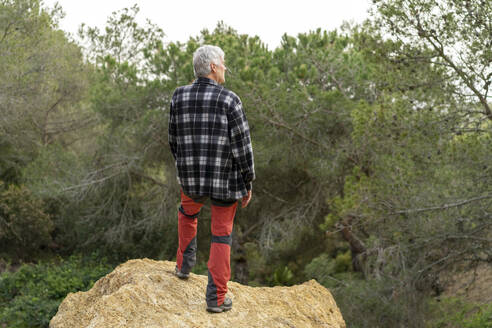Senior man on a hiking trip standing on a rock looking at view - AFVF06199