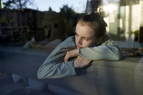 Serious girl on couch at home looking out of window - AUF00366