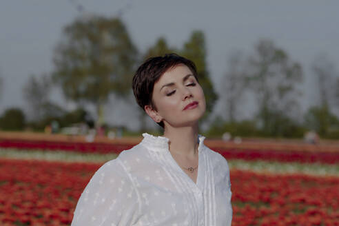 Portrait of woman with eyes closed in front of tulip field - OGF00343