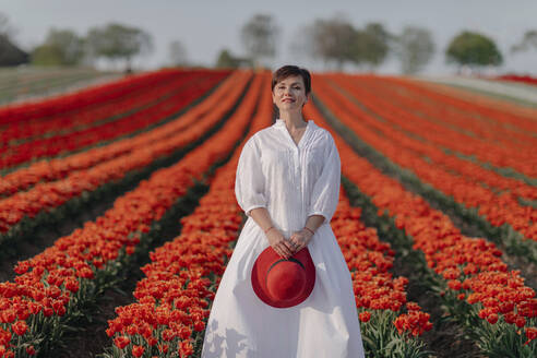 Portrait of smiling woman dressed in white standing in front of tulip field - OGF00346