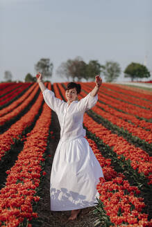 Portrait of smiling woman dancing in  tulip field - OGF00352