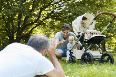 Senior man spending time with his adult son and his granddaughter in a park - DIGF10250