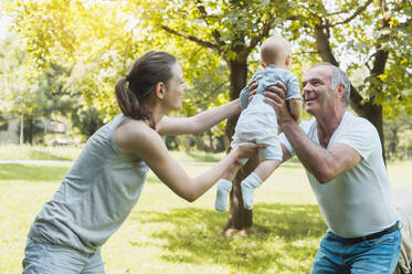 Senior man spending time with his adult daughter and his granddaughter in a park - DIGF10256