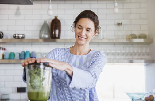 Smiling woman making healthy green smoothie in blender in kitchen - CAIF27045