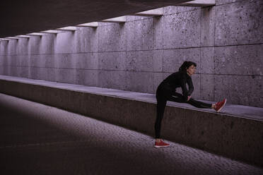 Female athlete warming up before running in pedestrian underpass - DHEF00165
