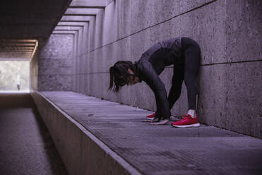 Female athlete warming up before running in pedestrian underpass - DHEF00183