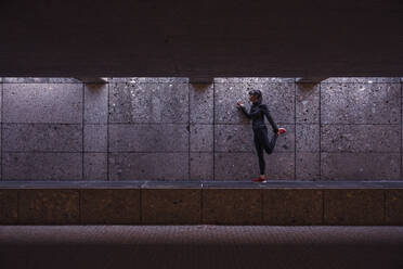 Female athlete warming up before running in pedestrian underpass - DHEF00186