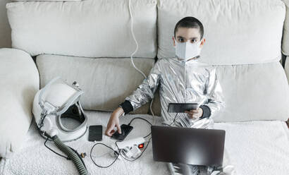 Boy playing game using laptop and smartphone, wearing space suit and protective mask - JCMF00678