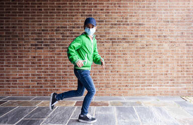 Boy wearing protective mask running in front of a brick wall - JCMF00681
