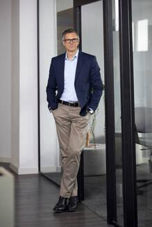 Portrait of confident mature businessman in office - RBF07633