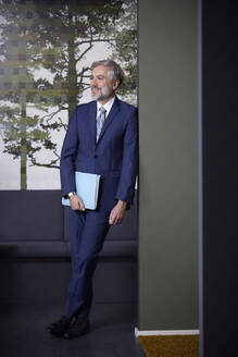 Smiling mature businessman holding folder in office - RBF07642